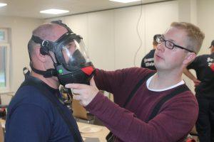 Die Feuerwehrleute helfen sich untereinander beim Anprobieren.